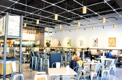 The restaurant features a modern setting with nconcrete floors, wall art and high tin ceilings.