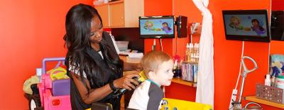Salon manager Dana Franklin gives 3-year-old Mason Herrin a haircut as he watches television.