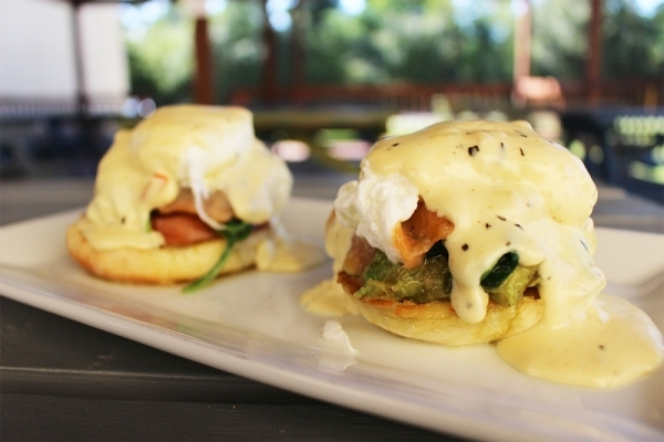 Smoked salmon, sauteed spinach, tomato slices and avocado are served on top of English muffin halves with two poached eggs and Cajun hollandaise sauce to create the Smoked Salmon Benedict.