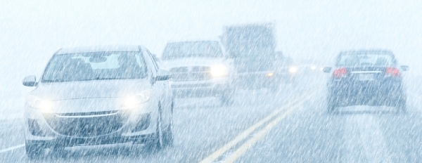 cars driving on wet and snowy highway