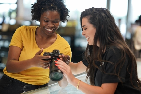 A photo of a salesperson showing a camera to a customer.