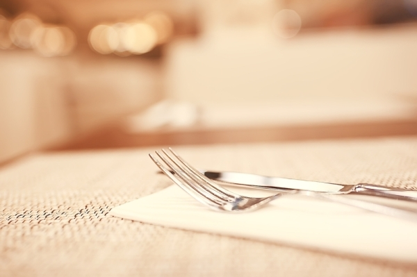 fors and knives on a napkin on a table with a tablecloth