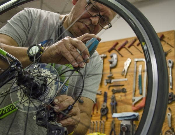 Nelo Breda, owner of Nelo's Cycles and Coffee, works on a repair.