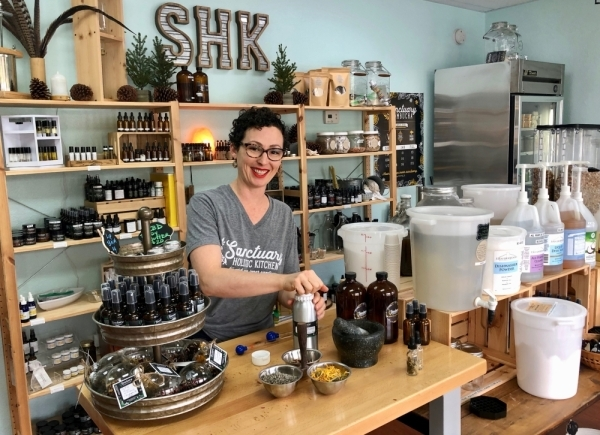 Owner Robin Cervantes works with products in the retail store at Sanctuary Holistic Kitchen. (Sally Grace Holtgrieve/Community Impact Newspaper)