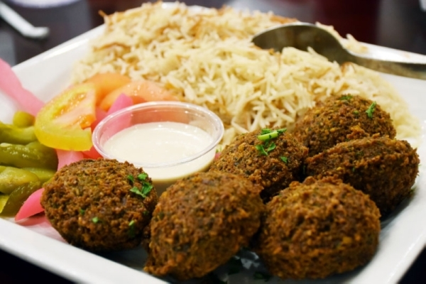 The falafel plate ($13.99 comes with tahini sauce and two sides. (Makenzie Plusnick/Community Impact Newspaper)