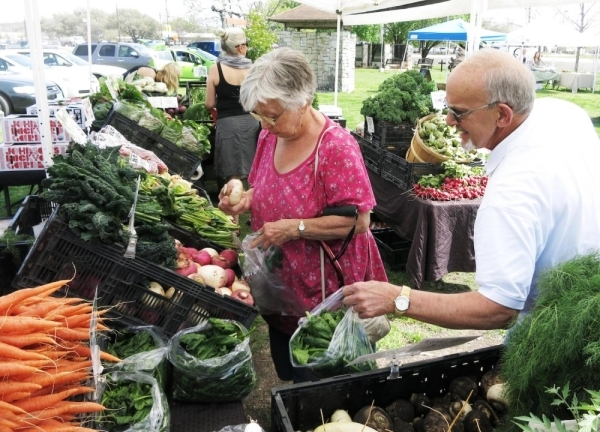 A photo of an older couple choosing produce