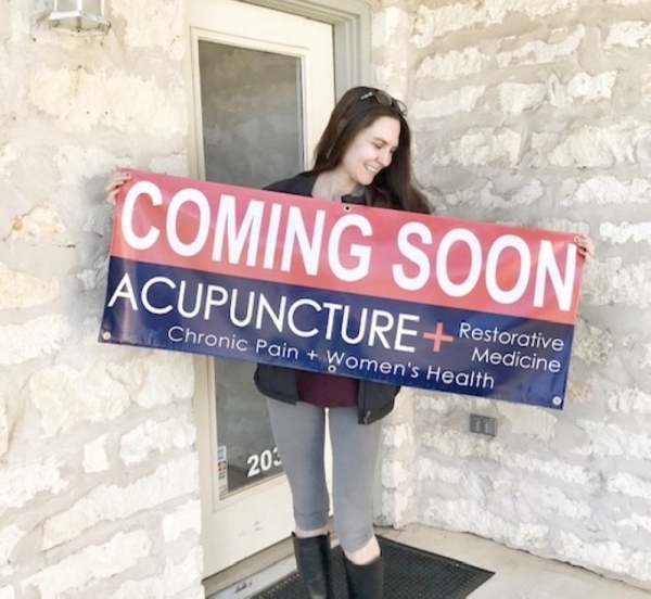 """A photo of a woman holding a """"coming soon"""" sign for Acupuncture + Restorative Medicine"""
