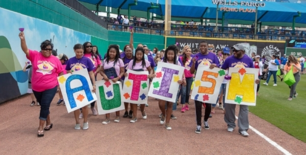 Montgomery's three daughters (center), who are all  diagnosed with autism spectrum disorder, walk in the annual Family Strike Out Parade. (Courtesy Hope Collins Montgomery)
