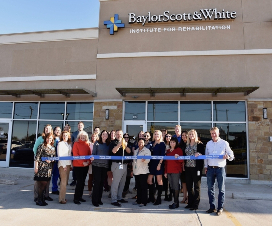 A photo of a group of people holding a ribbon, with one man getting ready to cut it with scissors, in front of a Baylor Scott & White Institute for Rehabilitation location.
