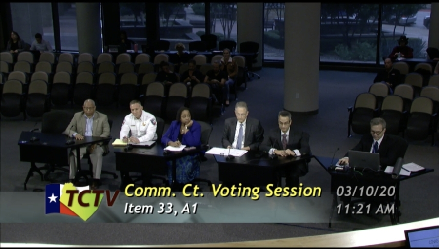 A photo of Travis County officials presenting to the commissioners court.