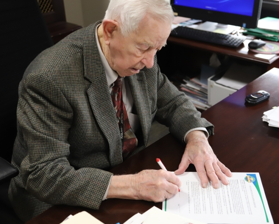 Mayor Tom Reid at a desk signing an official document