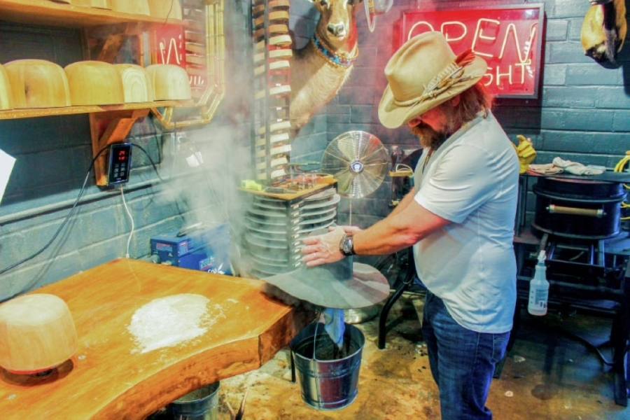 Ras Redwine of Aspen Hatter steams a hat to make the material more pliable in order to customize the fit. (Jack Flagler/Community Impact Newspaper)