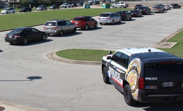 A Leander Police Department SUV is parked outside Bagdad Elementary School as vehicles line up during a Leander ISD student lunch giveaway March 25. (Brian Perdue/Community Impact Newspaper)
