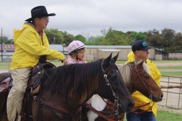 David Wiedenfeld and his granddaughter sit atop their horses while talking to Wiedenfeld's son-in-law, Wade Zaeske. (Warren Brown/Community Impact News)