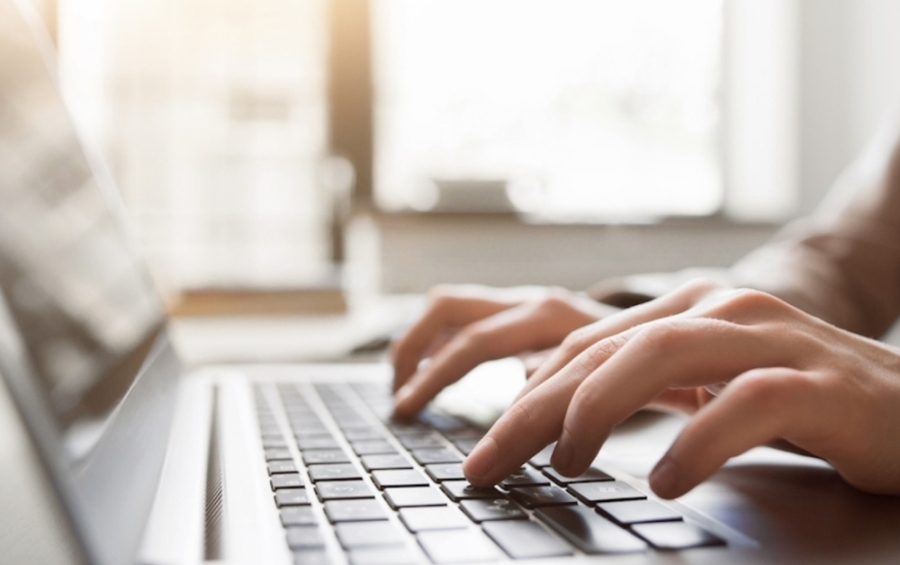 A photo of two hands typing on a laptop