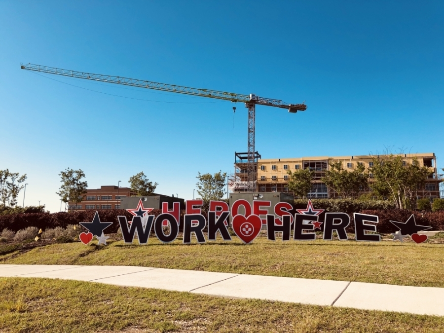 """Colorful yard signs decorate the roadside near Medical City Alliance hospital. The signs spell out, """"Heroes Work Here."""" (Ian Pribanic/Community Impact Newspaper)"""