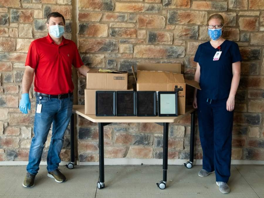 Matt Prause, LISD's director of hardware/software support, and Stephanie Herbison, representing Dell Seton Medical Center, are pictured with the donated iPads on May 4. (Courtesy Leander ISD)