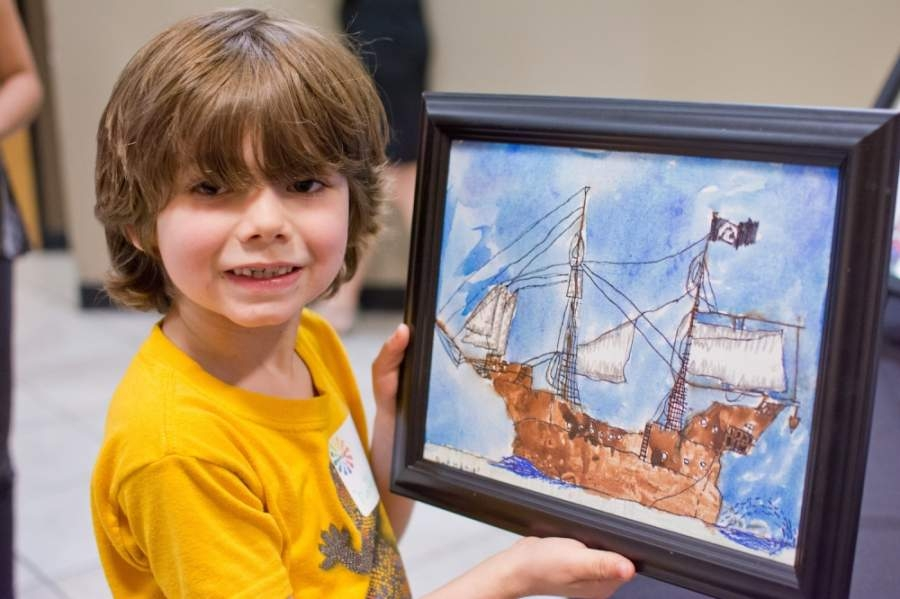 A photo of a young boy holding a painting of a ship