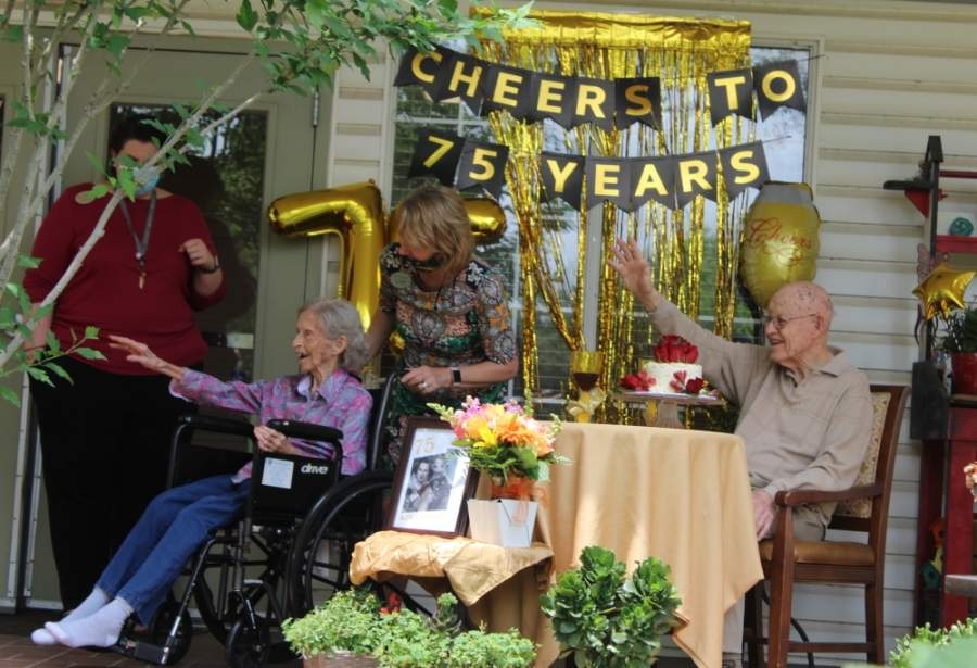 Denise and Carl Starnes, who celebrated their 75th wedding anniversary May 5, wave to their four great-grandchildren during a surprise, socially distant party at Brookdale Round Rock, an assisted-living facility where the couple reside. (Brian Perdue/Community Impact Newspaper)