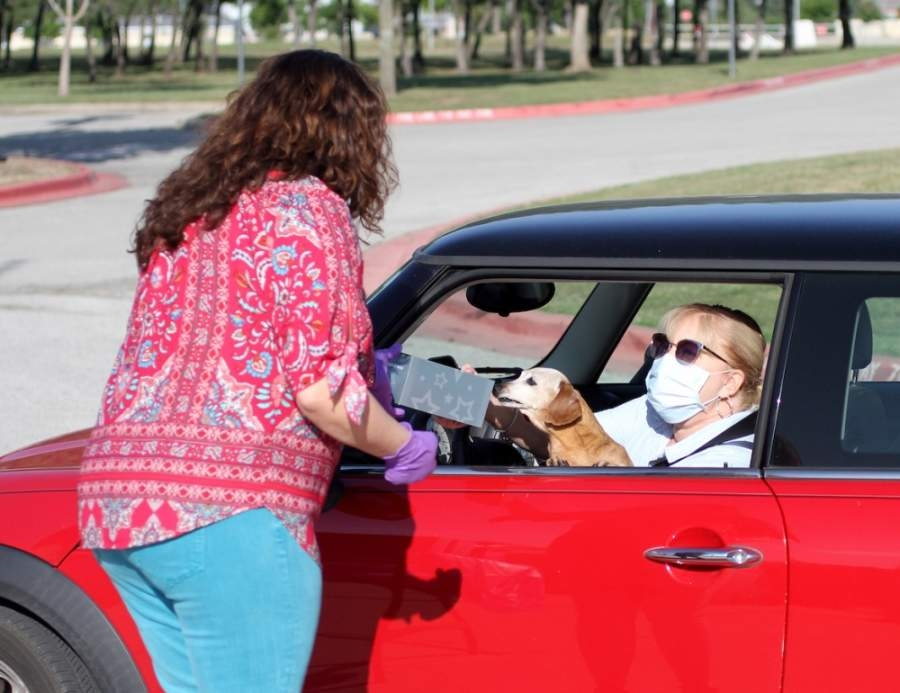 District nurse Cristin Wicketts hands a gift box to Knowles Elementary School nurse Julie Davis—and her dog Daisy—on May 6 at Vista Ridge High School in Cedar Park. (Courtesy Leander ISD)