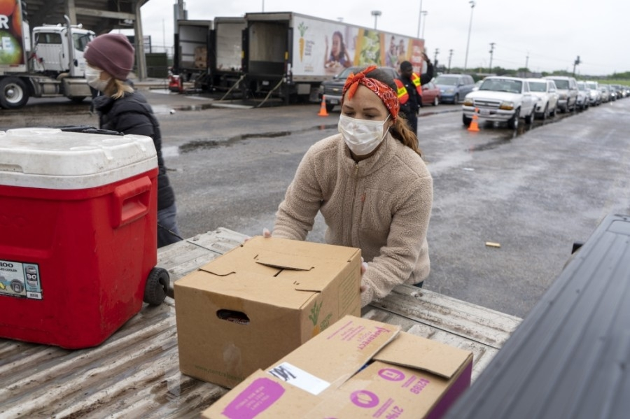 A volunteer unloads food from a truck during the Central Texas Food Bank's April 4 event to feed families in need at Nelson Field in Austin. (Courtesy Central Texas Food Bank)