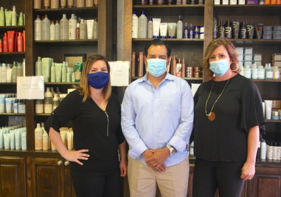 Amber Hall (left) is the area manager for the Salons at Stone Gate and The Factory Cypress. Her aunt and uncle Stephanie (right) and Gino Hernandez (middle) own both locations. (Danica Smithwick/Community Impact Newspaper)