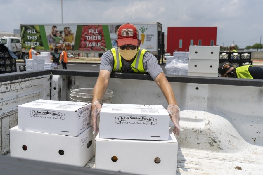 Volunteers help load food at an event hosted by the Central Texas Food Bank at Del Valle High School in April. (Courtesy Central Texas Food Bank)