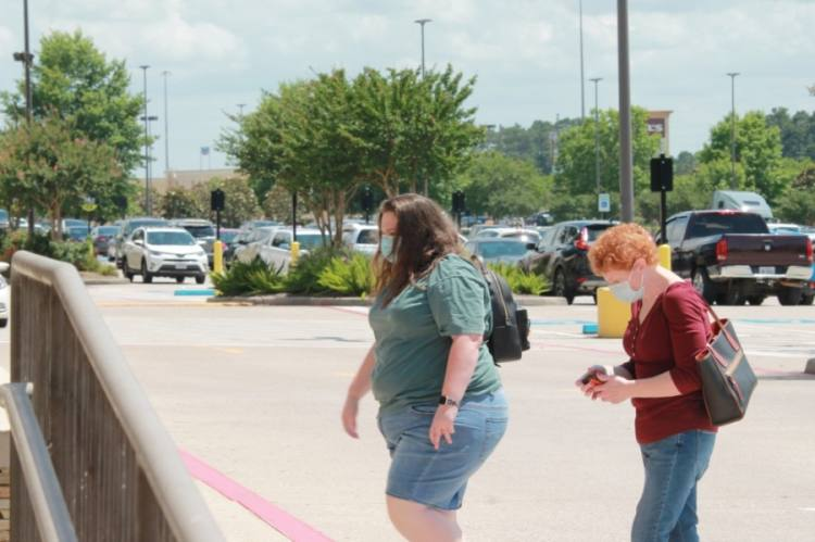 Residents walk through a shopping center in north Conroe wearing masks before Gov. Greg Abbott issued his statewide mask order. (Andy Li/Community Impact Newspaper)