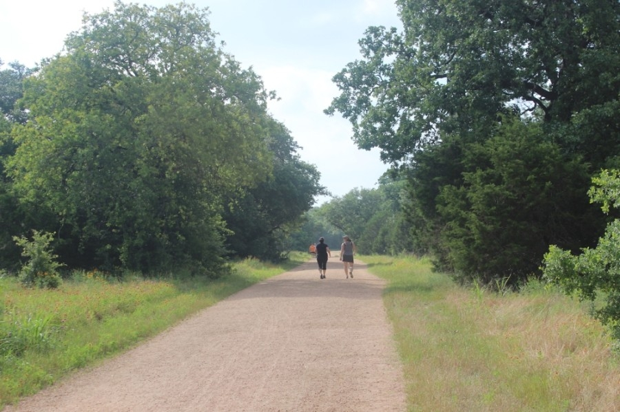 A photo of two women walking on a trail