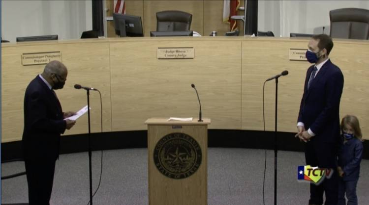Screen shot of two men and a little girl in the Travis County Commissioners Court chambers