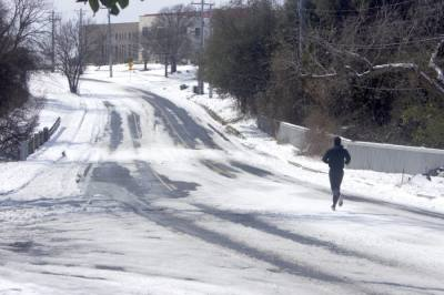 A lone runner jogs on a snow-covered road in Austin. Transportation projects across the city were briefly paused due to Winter Storm Uri. (Jack Flagler/Community Impact Newspaper)