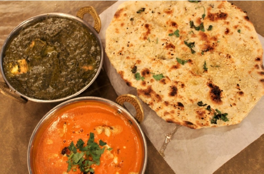 Two types of paneers, an Indian-style cottage cheese, •palak ($12.99) •and •butter masala ($12.99)•, are served with naan. (Photos by Sandra Sadek/Community Impact Newspaper)