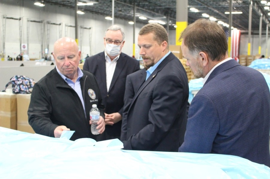 U.S. Rep. Kevin Brady and state Rep. Steve Toth examine a surgical isolation gown made at Wildcat PPE. (Andrew Christman/Community Impact Newspaper)