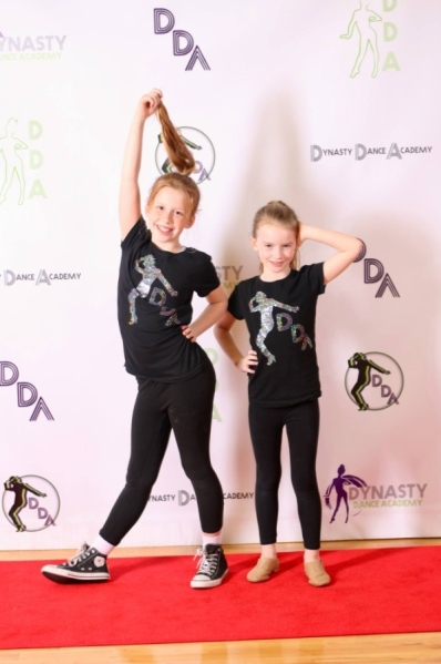 Two young dancers pose before a backdrop at the Dynasty Dance Academy Social.