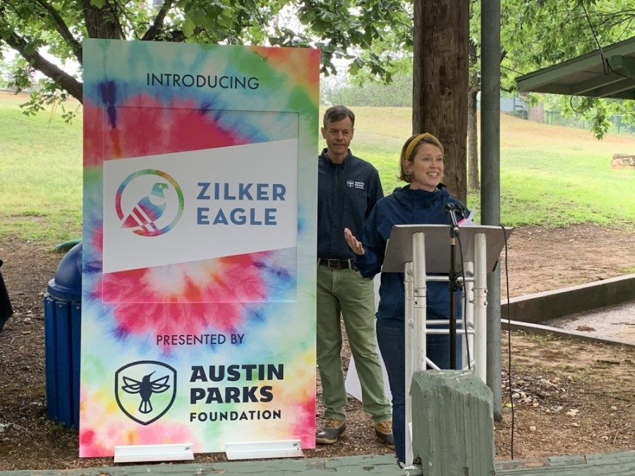 """Photo of a woman at a podium and a tie dye sign reading """"Zilker Eagle"""""""