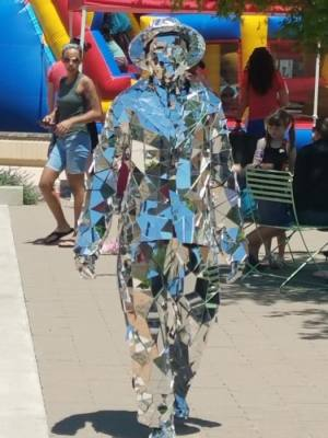 A man covered in mirrors walks towards the viewer.
