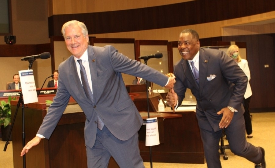 Former Mayor Harry LaRosiliere (right) hands off the gavel to new Mayor John Muns at the May 10 City Council meeting. (Erick Pirayesh/Community Impact Newspaper)