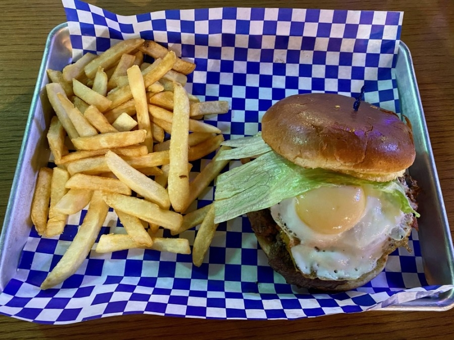 Old Town Burger ($10.95) includes a beef patty with caramelized onions, bacon, cheese, lettuce and tomatoes and topped with a fried egg on a brioche bun and a side of fries. (Yvonne Brown/Community Impact Newspaper)