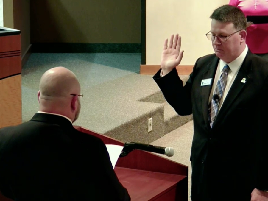 Dan Jaworski with his hand up while he is being sworn in.