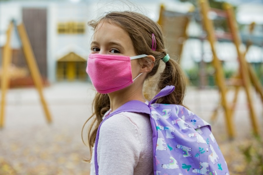 Photo of a girl weariing a mask and backpack