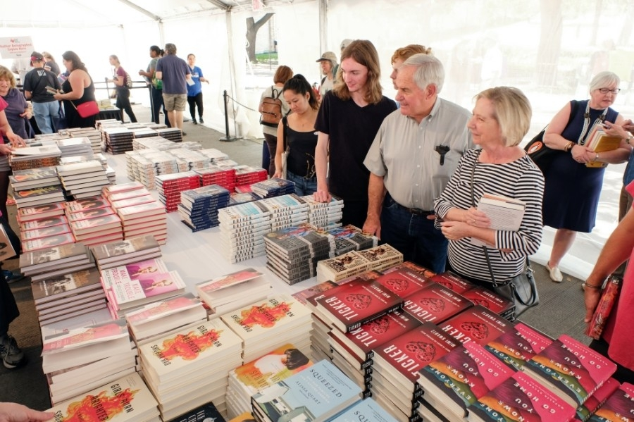 Photo of shoppers eyeing a table of books