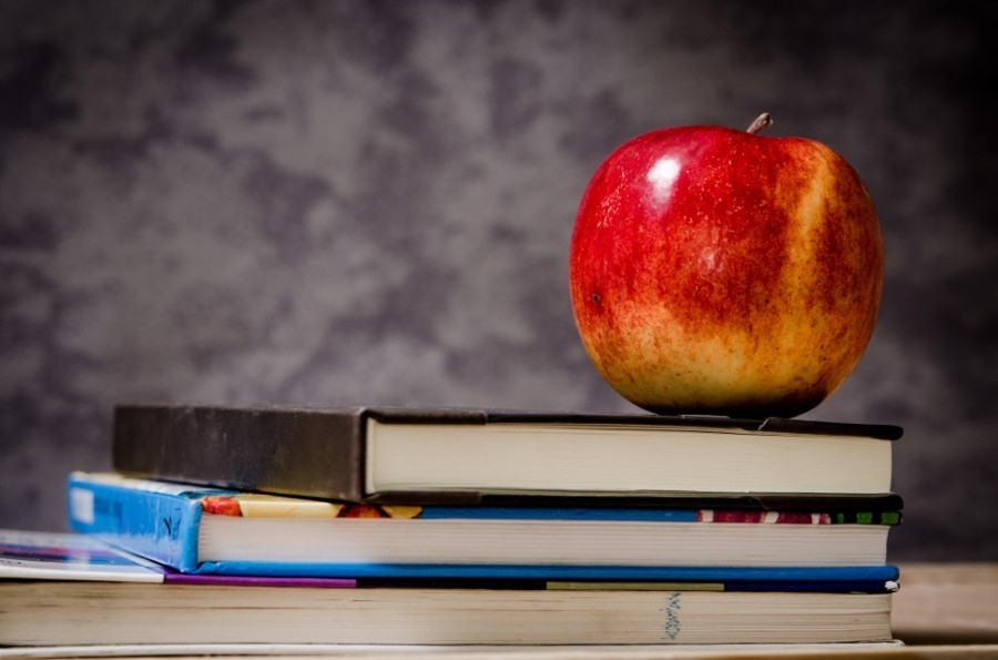 apple sitting on stack of books