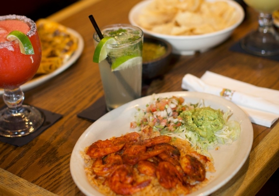 Plates of Mexican food and two drinks on a table