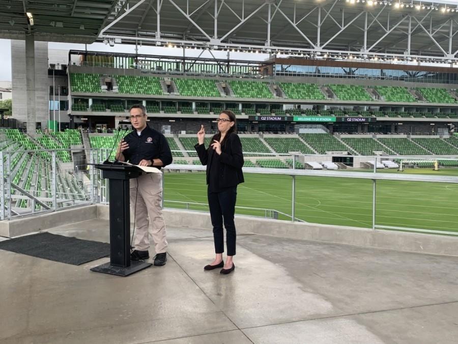 Photo of a man speaking and woman doing ASL interpretation at Q2 stadium