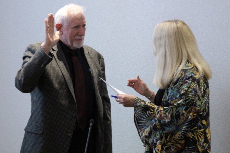 Mark Schluter raises his hand as he takes the oath of office