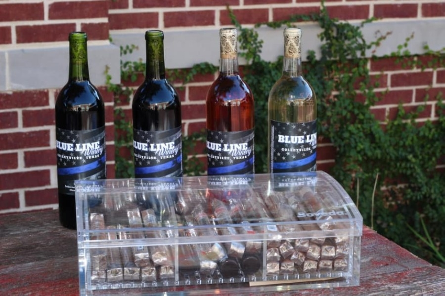 Four bottles of wine with Blue Line Winery labels and a clear box of cigars