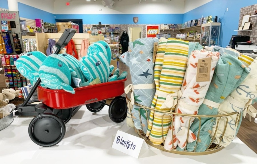 A basket of baby blankets and a red wagon with five small stuffed whales in it, both on a display shelf
