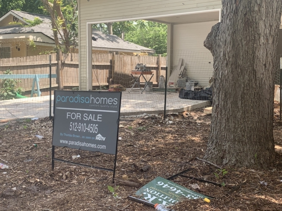 """Photo of a """"for sale"""" sign in front of an under-construction house"""