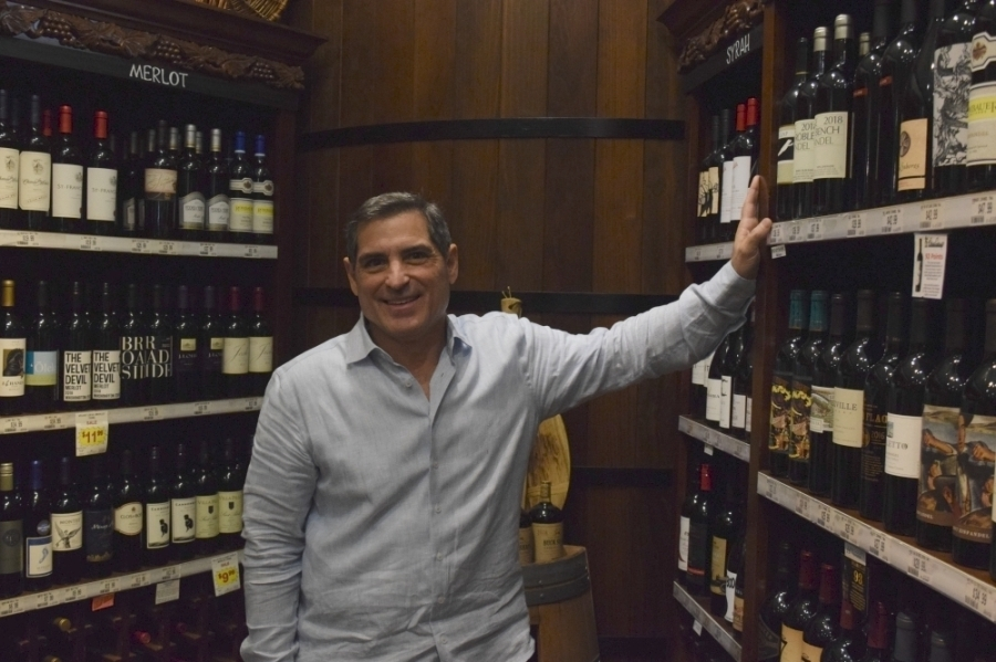 owner Randy Johnson stands next to some of the wine bottles his store has for sale
