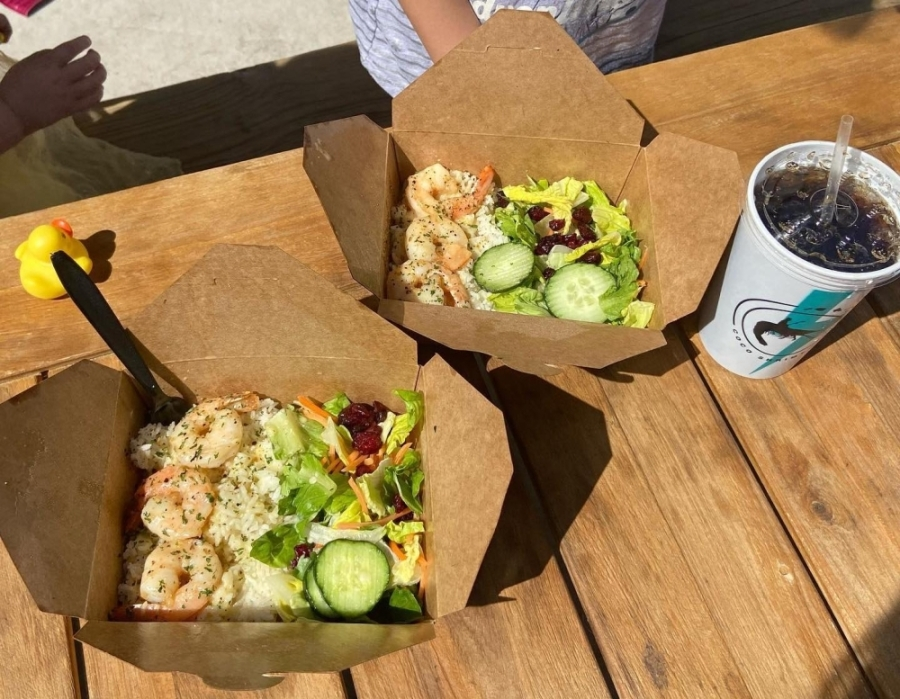 Cardboard to-go boxes of shrimp with rice and salad, on a table next to a cup of soda and a rubber duck